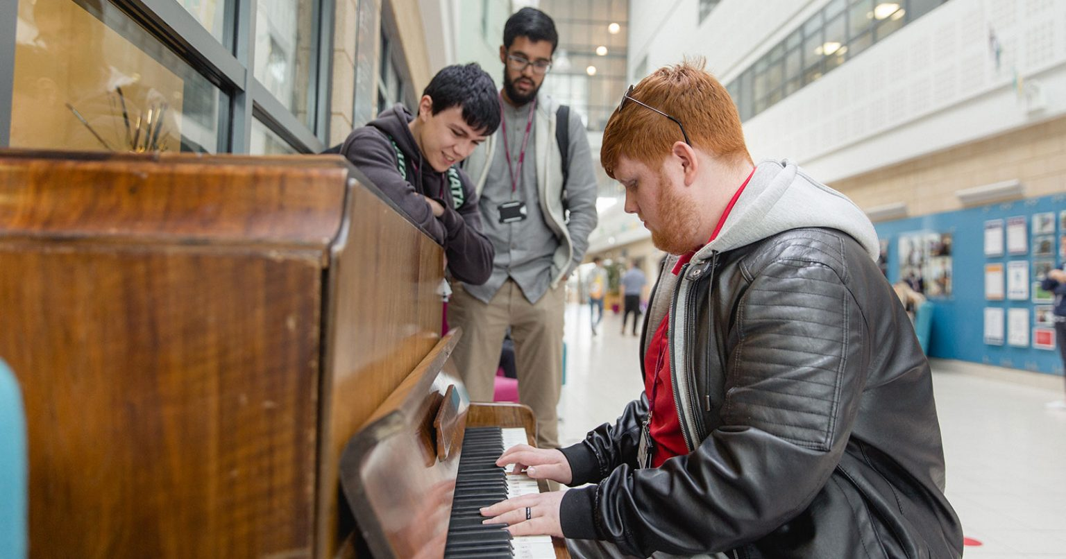 Keighley College student playing the piano at Keighley College with other students watching